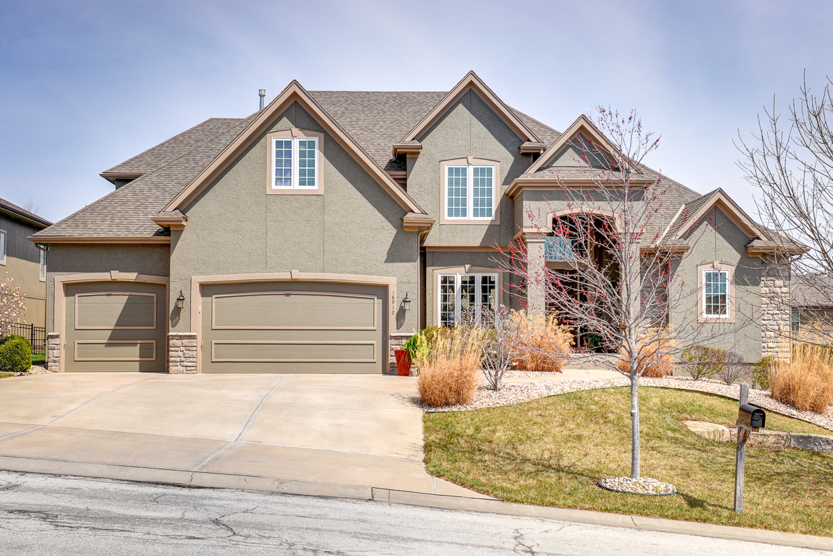 Gorgeous 5,200 square-foot home for sale with spacious driveway, custom landscaping, and four large living areas.